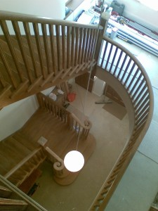 This image shows a view of both oak cut string staircases from the top floor, and from here, you can also see the curved oak gallery handrail. In case you're wondering, the white blob is a pendant lampshade suspedned from the ceiling above!