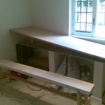 "First ""L"" shaped section of oak-faced MDF worktop being fitted"